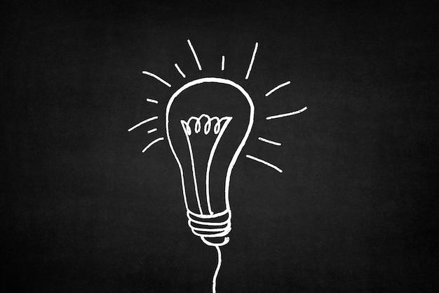 Ampoule blanche tracée sur un tableau noir,