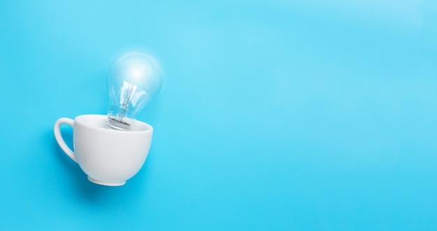 Ampoule dans une tasse blanche sur fond bleu. idées et concept de pensée créative.