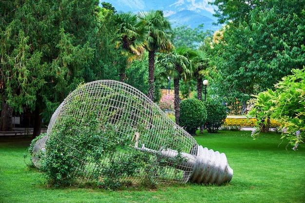 Ampoule décorative dans les plantes vivantes sur une pelouse avec des arbres et des buissons épais.