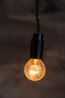 Ampoule décorative de style edison sur le fond de mur sombre. détails intérieurs du loft