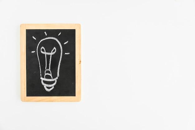 Ampoule dessiné à la craie sur ardoise sur fond blanc