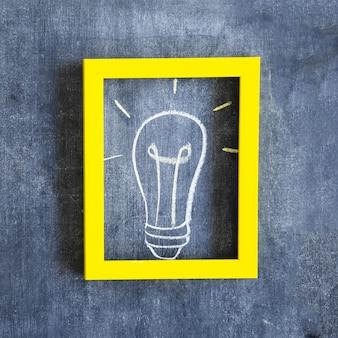 Ampoule dessiné à la main à l'intérieur du cadre avec bordure jaune sur le tableau noir