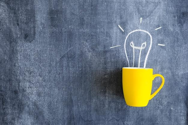 Ampoule dessinée sur la tasse jaune sur le tableau noir