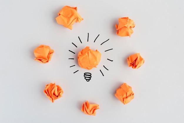 Ampoule avec du papier coloré froissé sur une surface blanche