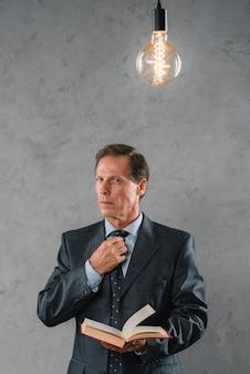 Ampoule éclairée sur l'homme d'affaires mature tenant un livre debout sur fond gris