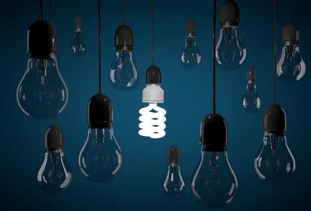 Une ampoule à économie d'énergie éclairant une ampoule à incandescence sombre suspendue à des fils sur fond bleu