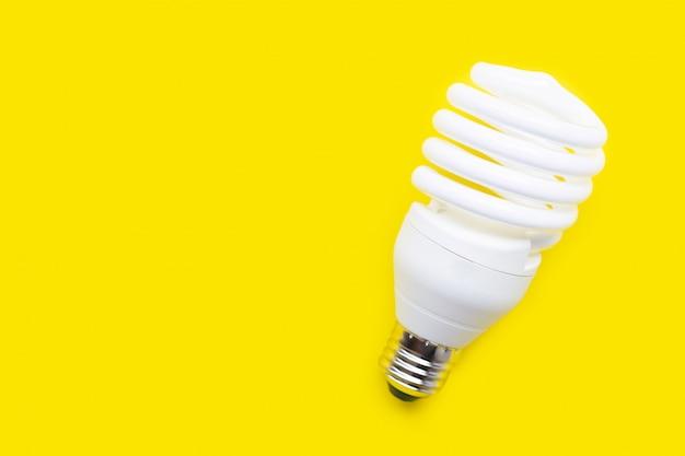 Ampoule à économie d'énergie sur fond jaune.
