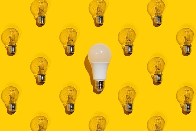 Une ampoule économique et de nombreuses lampes à incandescence sur fond jaune. concept d'idée.