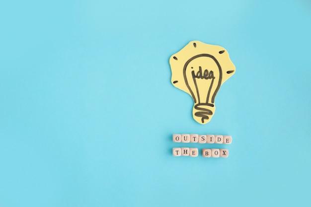 Ampoule d'idée dessiné main à l'extérieur du texte de la boîte faite avec des blocs sur fond bleu