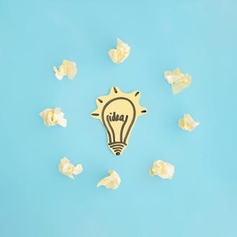 Ampoule d'idée entourée de papier froissé sur fond bleu