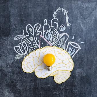 Ampoule jaune sur le cerveau avec des légumes dessinés sur le tableau noir