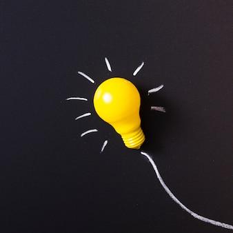 Ampoule jaune éclairée sur tableau noir