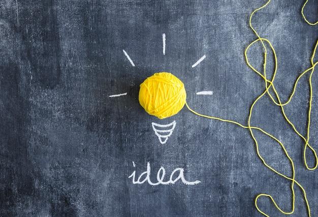 Ampoule jaune faite avec une pelote de laine avec le texte de l'idée sur le tableau noir