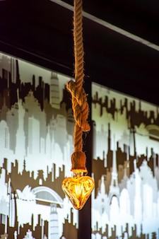 Ampoule jaune en forme de coeur suspendu avec une corde.