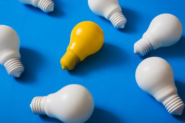 Ampoule jaune parmi les ampoules blanches sur fond bleu