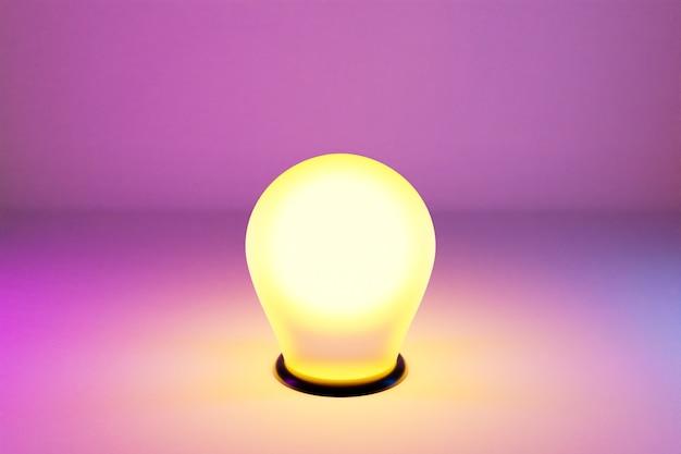 Une ampoule jaune vif est allumée sur un fond rose isolé. la lumière du renfoncement brille intensément