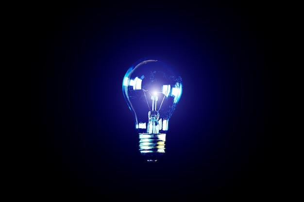 Ampoule de lampe sur fond noir. carte à l'intérieur. nouveau concept d'idée.