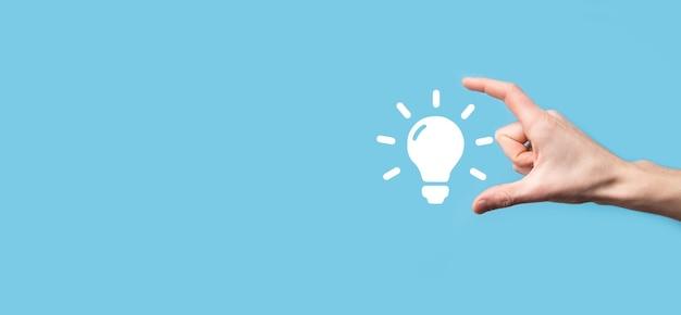 Ampoule à main. tient une icône d'idée brillante dans sa main. avec une place pour le texte. le concept de l'idée d'entreprise. concepts d'innovation, de remue-méninges, d'inspiration et de solution.