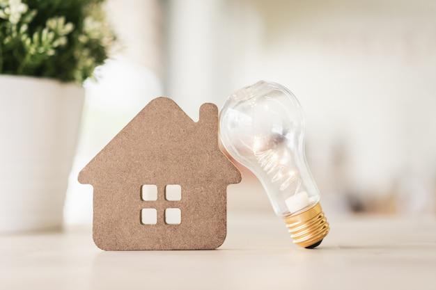 Ampoule avec maison en bois sur la table,