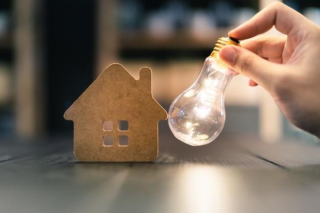 Ampoule avec maison en bois sur la table