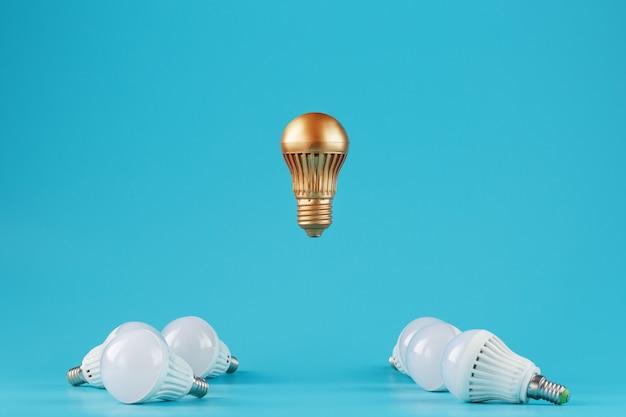 Une ampoule d'or proéminente lévite au-dessus d'un environnement d'ampoules à led blanches.