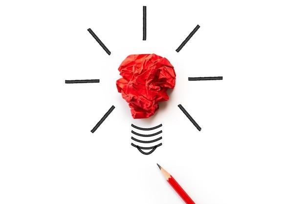 Ampoule avec papier coloré froissé et crayon rouge sur fond blanc.