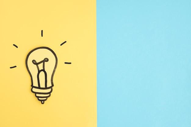 Ampoule de papier découpé sur fond jaune et bleu