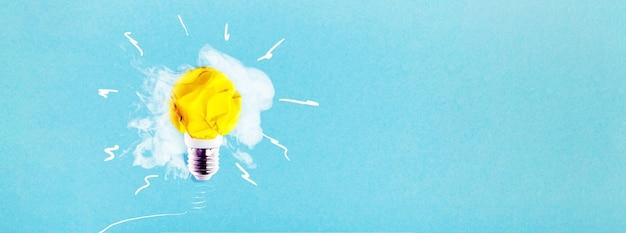 Ampoule de papier jaune froissé sur fond bleu avec de la fumée, idée de concept, maquette panoramique avec espace pour le texte