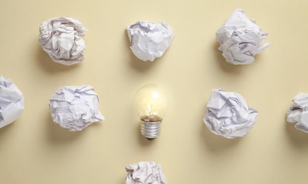 Ampoule et papiers froissés sur fond jaune.