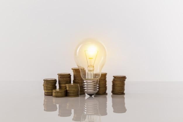 Ampoule avec piles de pièces sur tableau blanc