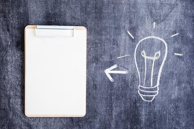 Ampoule et presse-papiers dessinés à la main sur tableau noir