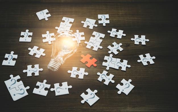 Ampoule avec puzzle rouge et point d'interrogation sur puzzle sur bois
