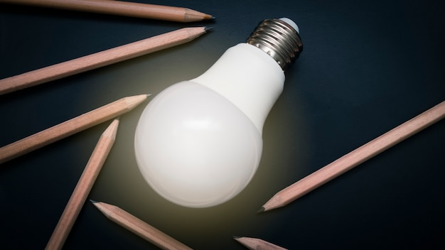 Ampoule rougeoyante sur tableau noir avec des crayons, concept idée et inspiration