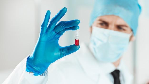 Ampoule avec un vaccin entre les mains d'un scientifique