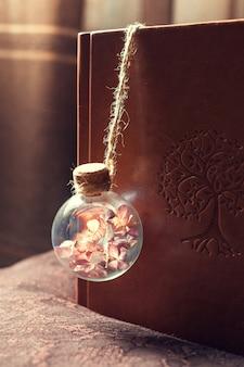 Ampoule en verre avec des fleurs séchées à l'intérieur sur une couverture de livre