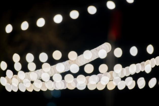 Ampoules dorées dans la nuit noire. lumières de la ville. bokeh doux