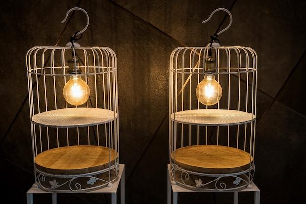 Ampoules électroniques sur cage suspendue blanche décorée sur support de table et mur noir. décoration intérieure sur bâtiment moderne.