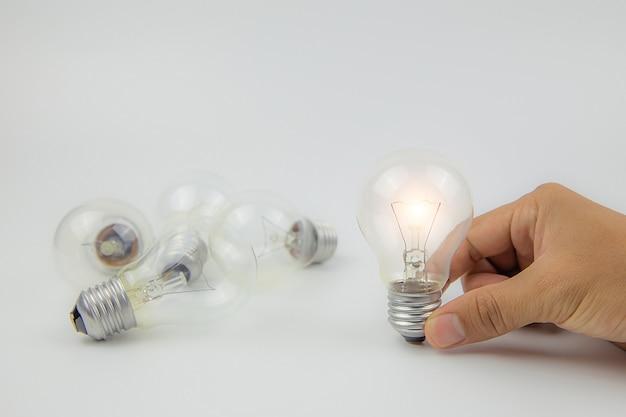 Ampoules avec lumière vive dans le concept de la main pour la créativité.