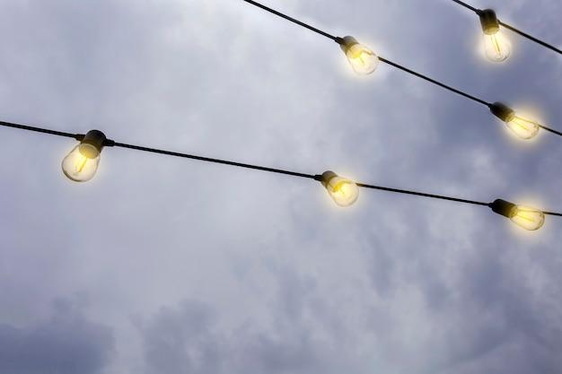 Ampoules lumineuses suspendues contre le ciel sombre du soir dans une rangée décoration moderne avec espace de copie