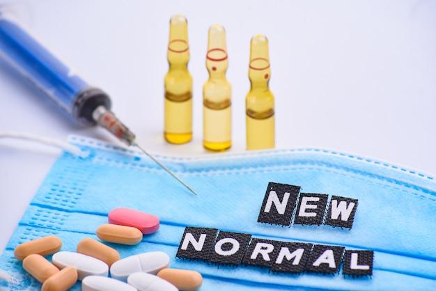 Ampoules médicales pour injection, nombreuses pilules, seringue et masque médical avec inscription new normal. médicaments et traitement des maladies. pharmacologie et science