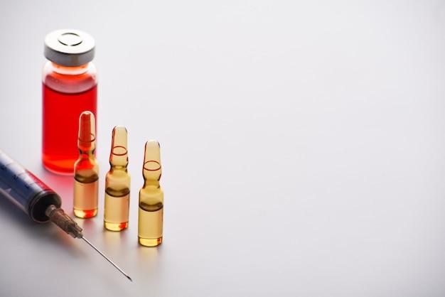 Ampoules médicales avec seringue isolé sur fond blanc. flacon médical et ampoules pour injection et seringue. médicaments et traitement des maladies. pharmacologie et science. copiez l'espace.