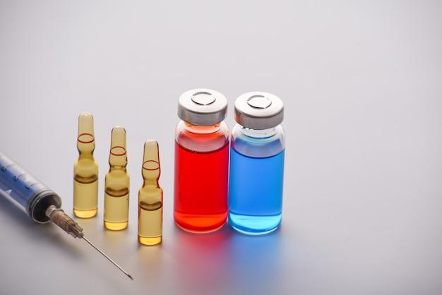 Ampoules médicales avec seringue isolé sur surface blanche. flacon médical et ampoules pour injection et seringue. médicaments et traitement des maladies. pharmacologie et science. copiez l'espace.