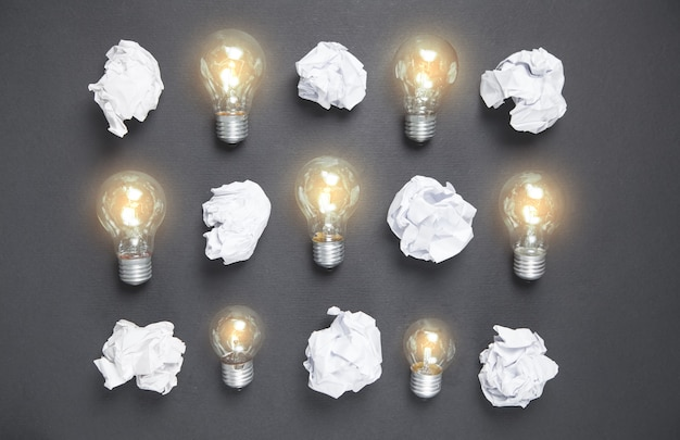 Ampoules et papiers froissés sur la surface noire