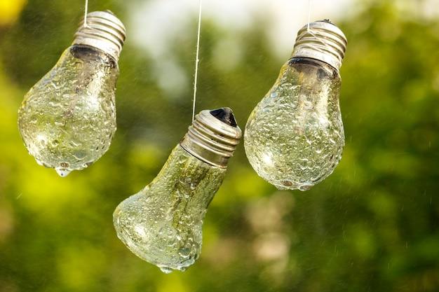 Les ampoules pendent au visage mouillé par la pluie sur un fond naturel.