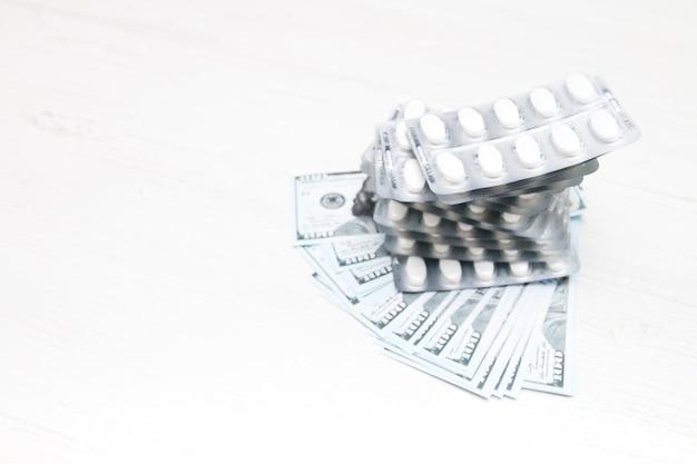 Ampoules de pilules et d'argent sur la table, billets d'un dollar