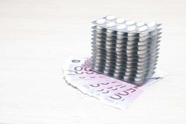 Ampoules de pilules et d'argent sur la table, factures en euros