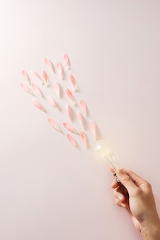 Ampoules pour économiser de l'énergie avec des fleurs autour sur fond rose