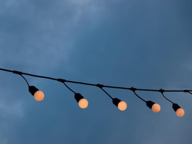 Ampoules suspendues à un fil électrique sur fond de ciel nuageux
