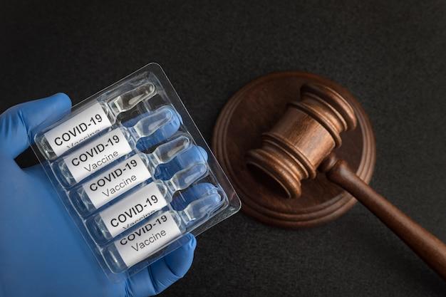 Ampoules avec vaccin pour coronavirus et marteau des juges. lois et décisions contre covid-19