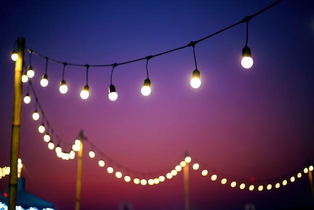 Ampoules Vintage Sur Fil De Chaîne Au Crépuscule à L'extérieur Photo Premium